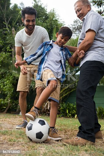 829627936istockphoto Low angle view of family playing soccer in yard 847913540