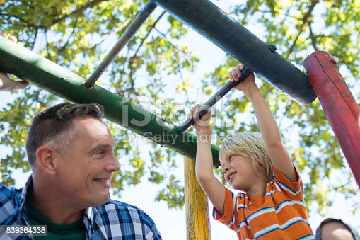 istock Low angle view of father and son playing on jungle gym 839364338