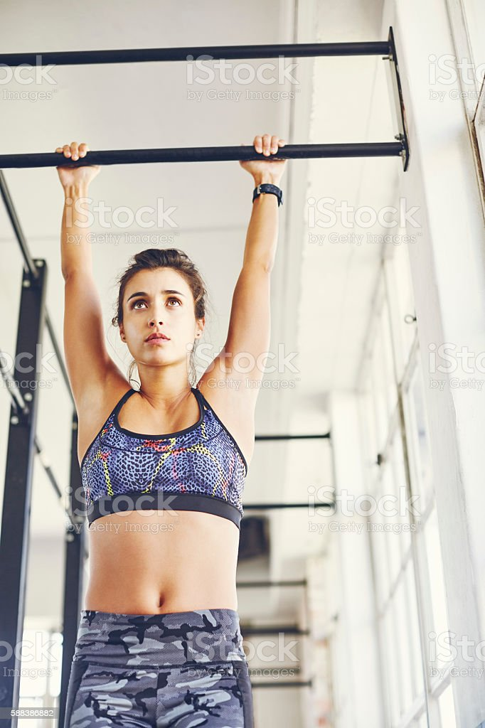 Low Angle View Of Fit Woman Doing Pullups In Gym Stock Photo
