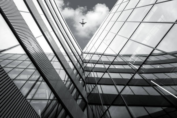 low angle view of flying airplane over modern architecture build - high contrast stock pictures, royalty-free photos & images