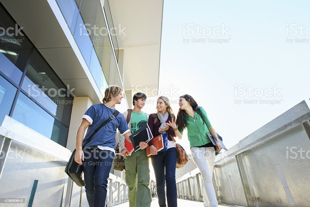 Low angle view of four university students on campus stock photo