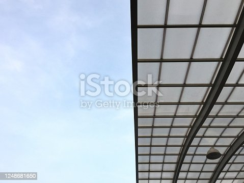 Low angle view of half-open glass ceiling with sky background
