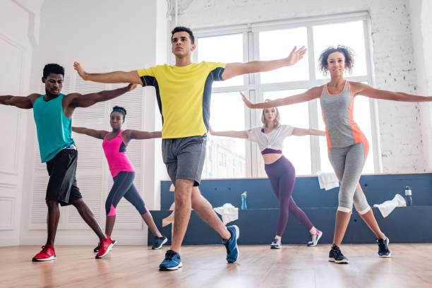 Low angle view of handsome trainer performing zumba with multicultural dancers in studio Low angle view of handsome trainer performing zumba with multicultural dancers in studio dance studio stock pictures, royalty-free photos & images