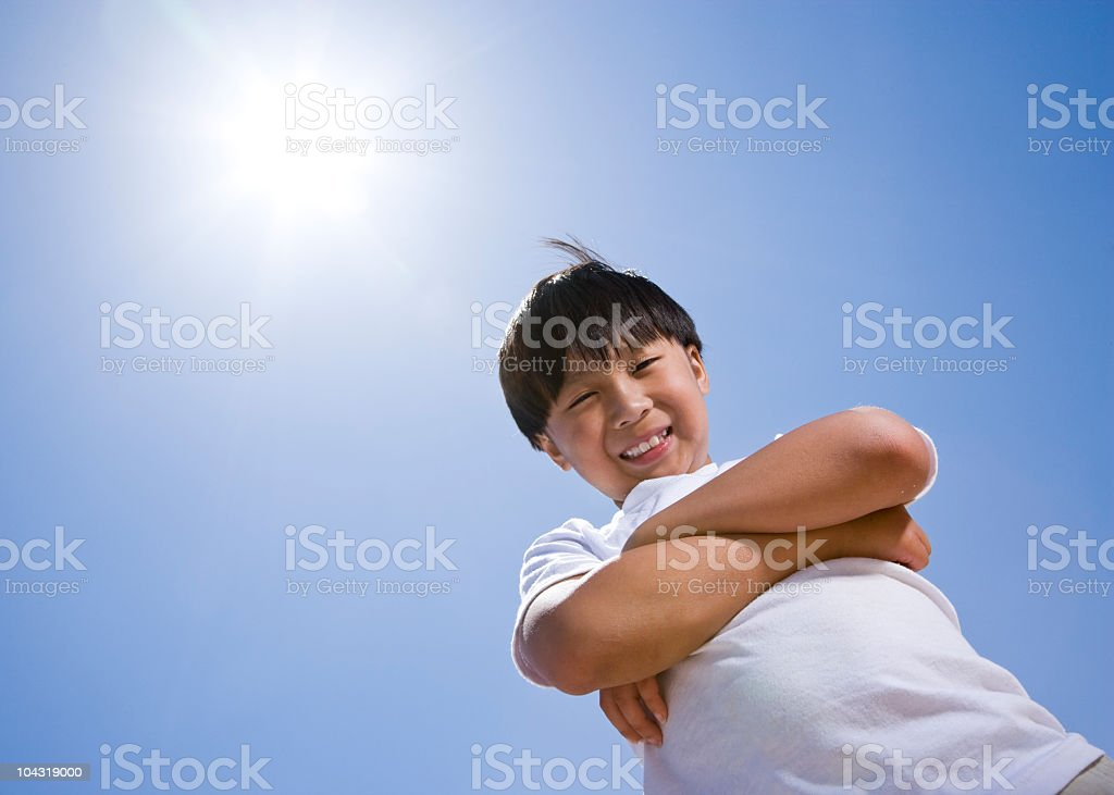 Low angle view of happy Asian boy with arms folded, blue sky behind