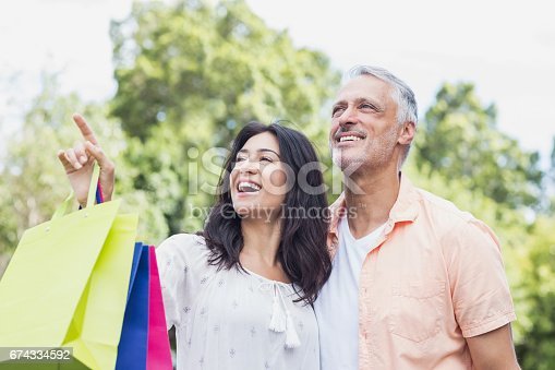 istock Low angle view of happy couple looking away 674334592