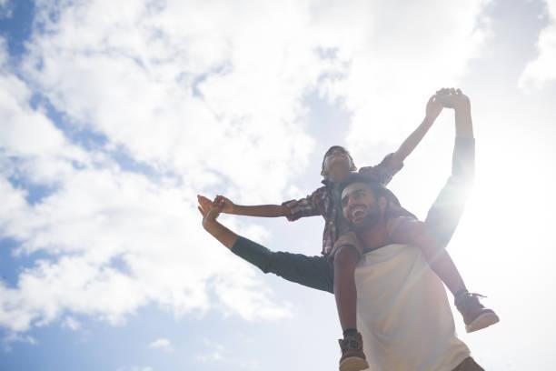 vue faible angle de heureux père portant des fils sur l'épaule - nuage 6 photos et images de collection