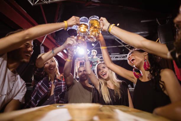 ビールのグラスをテーブルに座って乾杯幸せな友人の低角度のビュー ストックフォト