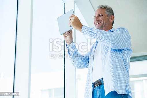 istock Low angle view of happy mature man holding tablet 653291058