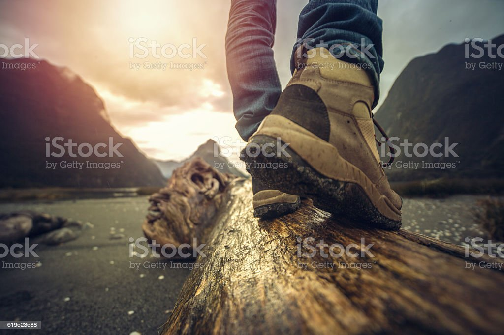 Low angle view of hiker standing on log, mountain scenery stock photo