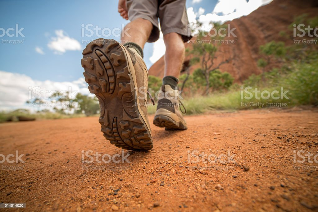 Low angle view of hiker's boots walking on dirt road stock photo