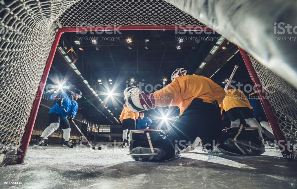 Low angle view of ice hockey player about to shoot at the goal. stock photo