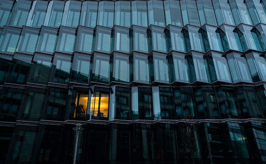 Low angle view of illuminated window in a modern building at dawn, Berlin, Germany