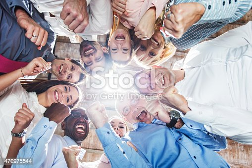 Below view of large group of happy business people celebrating their success and looking at the camera.