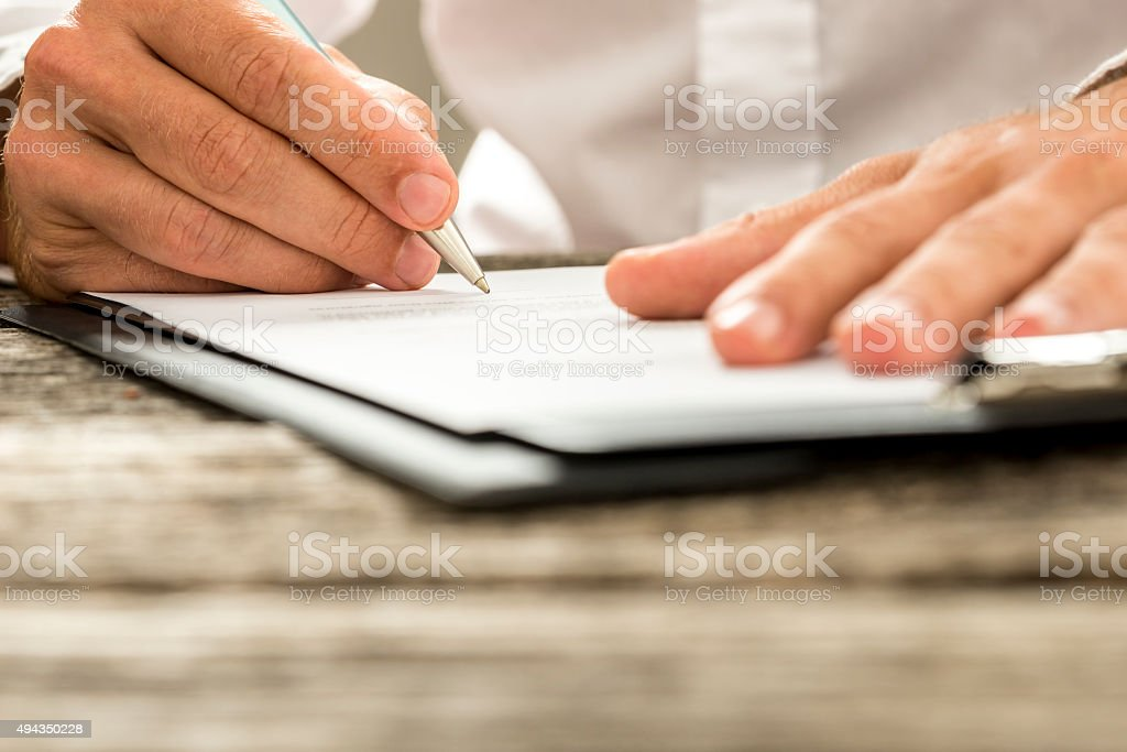 Low angle view of male hand signing contract or subscription stock photo