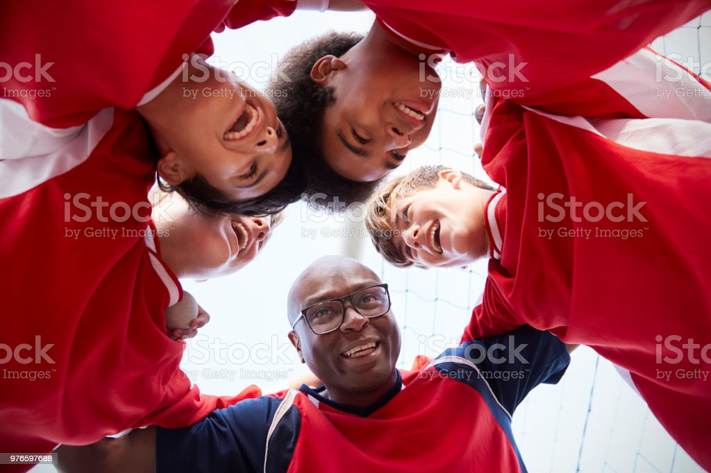 Low Angle View Of Male High School Soccer Players And Coach Having Team Talk stock photo