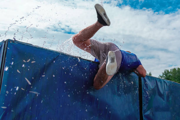Low angle view of man getting out of the water obstacle against sky during an extreme mud race. Rear view. Low angle view of man getting out of the water obstacle against sky during an extreme mud obstacle race. Rear view. obstacle course stock pictures, royalty-free photos & images