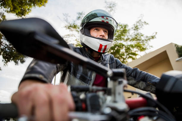 low angle view of man riding motorcycle - crash helmet stock photos and pictures