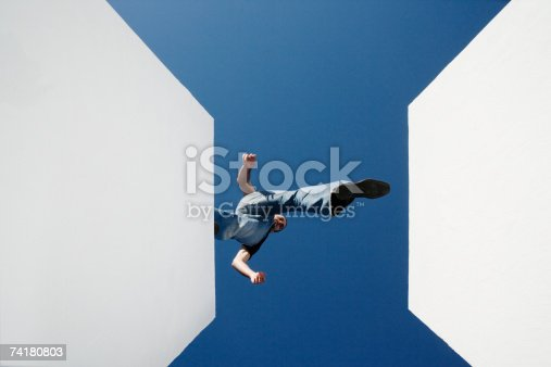 istock Low angle view of man walking across high gap outdoors 74180803