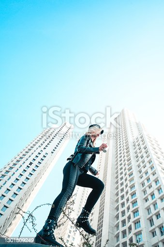 Low Angle View Of Modern Female Traversing Urban Grounds Among Skyscrapers