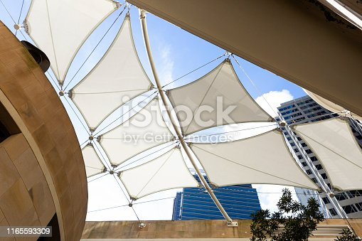 Low angle view of white modern sunshades between office buildings, background with copy space, full frame horizontal composition
