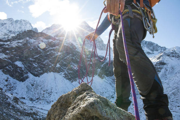 low angle view of mountain climber with rope in mountains - arrampicata su roccia foto e immagini stock