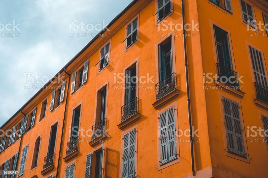 low angle view of orange apartment house with cloudy sky stock photo