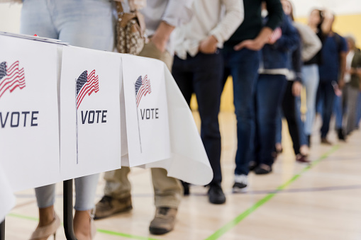 Low Angle View Of People Lined Up To Vote Stock Photo - Download Image Now