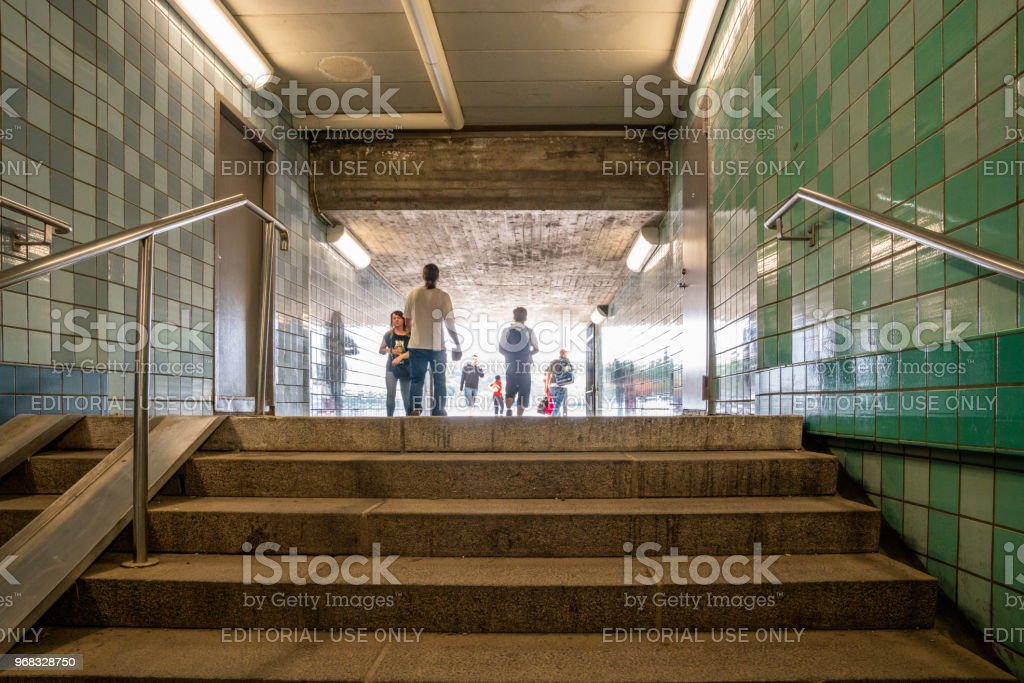 Low angle view of people passing throgh a subway underpass. stock photo