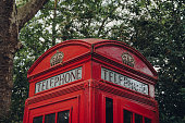 London, UK - June 20, 2020: Low angle view of red phone box against trees. Red phone boxes can be found in current or former British colonies around the world.