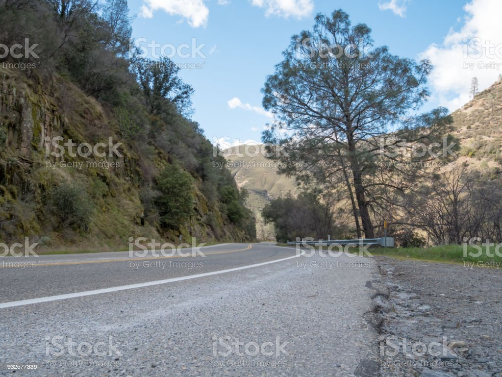 Low Angle View of Road That Curves Right With Large Mountains on each Side stock photo