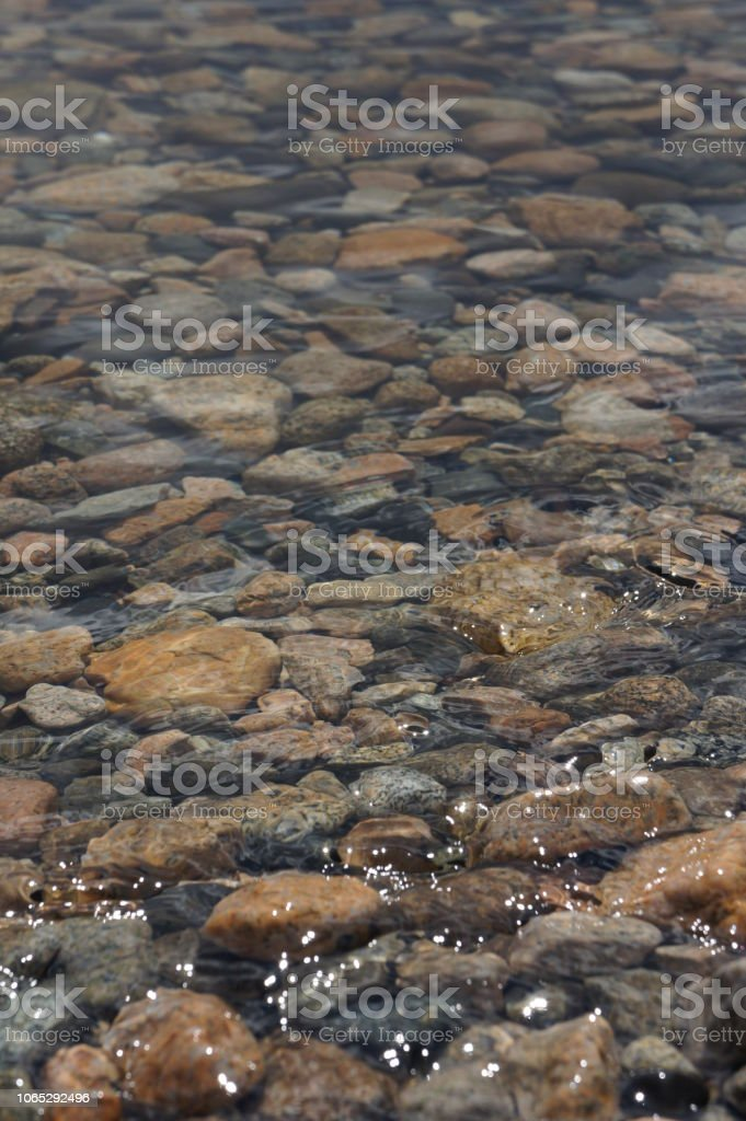 Low angle view of rocks and stones under flowing water in a creek stock photo