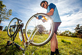 Low Angle View of Senior Man With Flat Bicycle Tire on a Meadow.