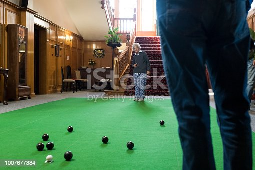 Photo of a low angle view of senior woman playing carpet bowls