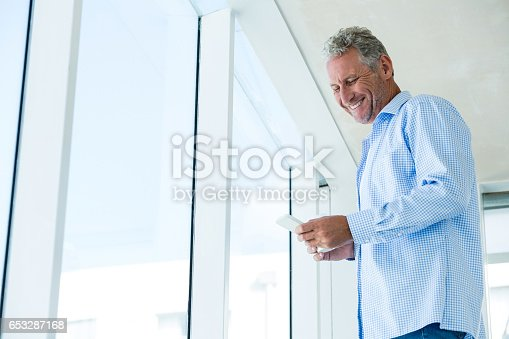 istock Low angle view of smiling man using phone 653287168