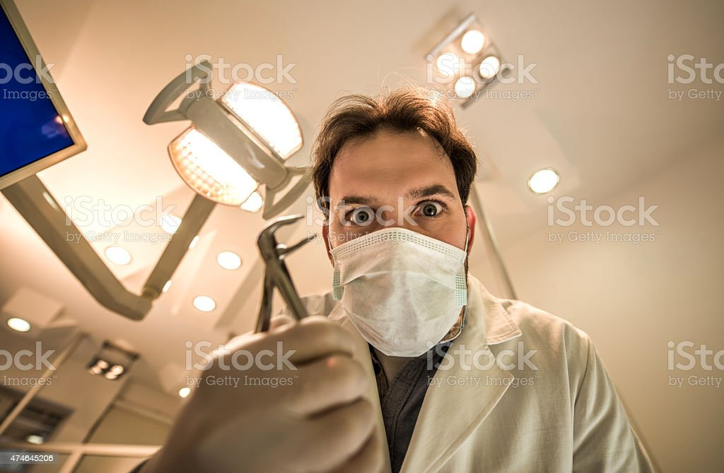 Low angle view of spooky male dentist with pliers. stock photo