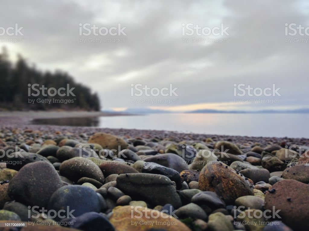 Low angle view of stones on a beach by the ocean stock photo