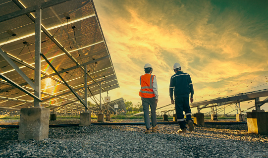 Low angle view of technician walks with investor through field of solar panels, Alternative energy to conserve the world's energy, Photovoltaic module idea for clean energy production.