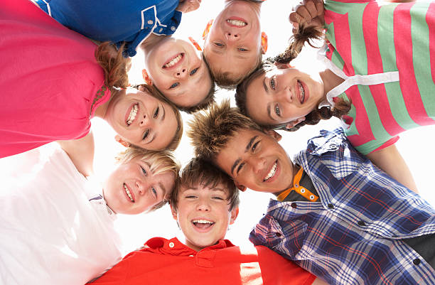 Low angle view of teenagers in circle stock photo