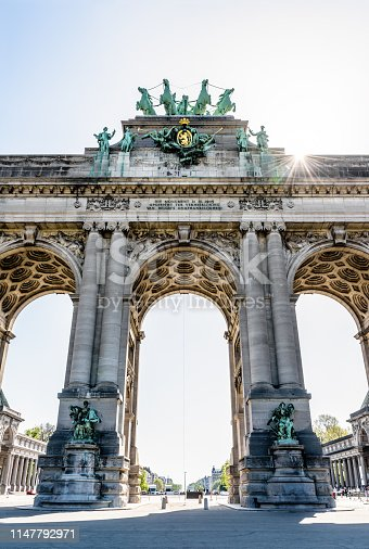Low angle view of the western side of the arcade du Cinquantenaire, the triumphal arch erected in 1905 by king Leopold II in the Cinquantenaire park in Brussels, Belgium, against the sunlight.