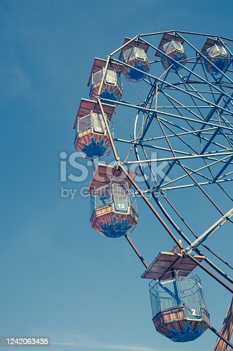 A low angle view of a vintage Ferris Wheel fairground ride with enclose seating under a blue sky and vertical composition