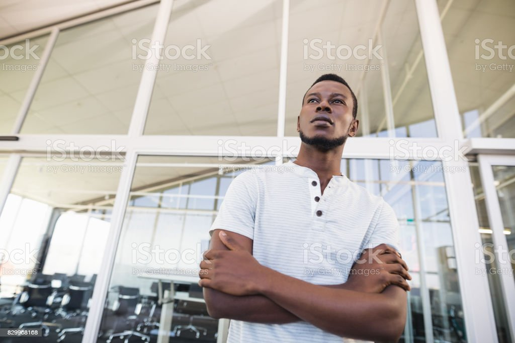 Low angle view of thoughtful businessman with arms crossed stock photo