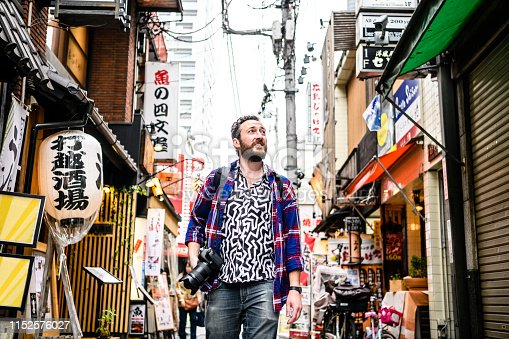 Mid adult man carrying camera and looking around busy street with Japanese signs, sight seeing, exploration, inspiration