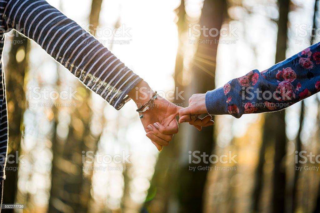 Low angle view of two female friends holding pinkies stock photo