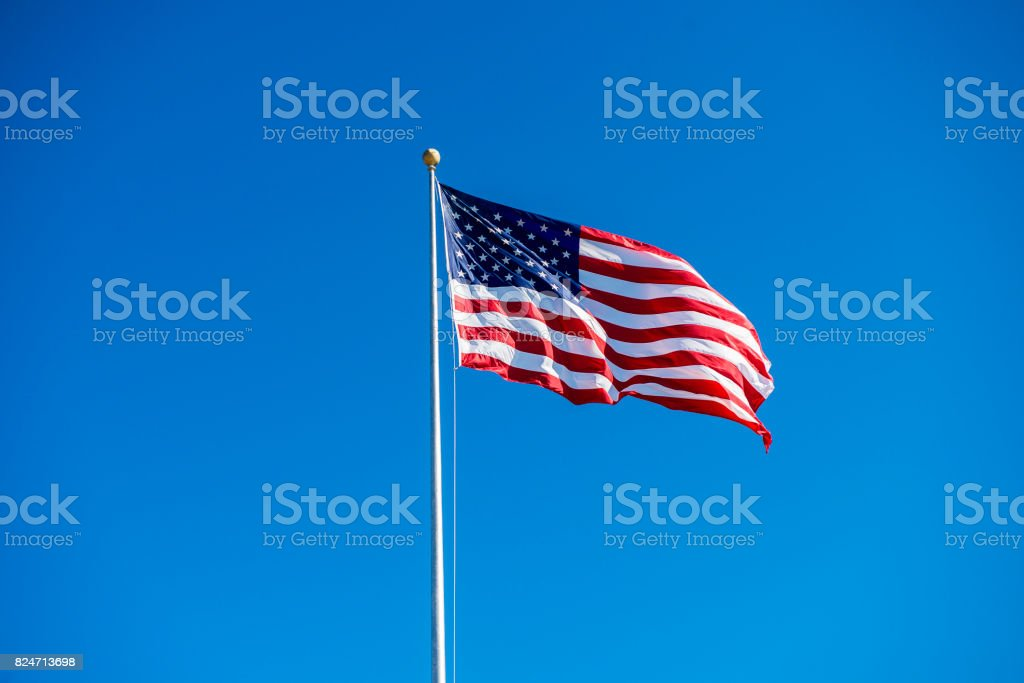 Low angle view of vawing American flag against clear sky during daytime stock photo