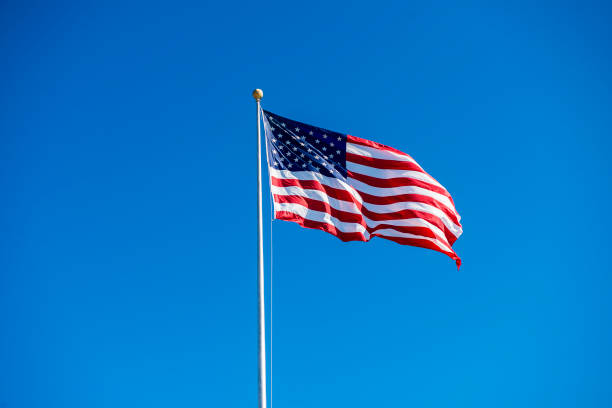 low angle view of vawing american flag against clear sky during daytime - usa flag stock photos and pictures