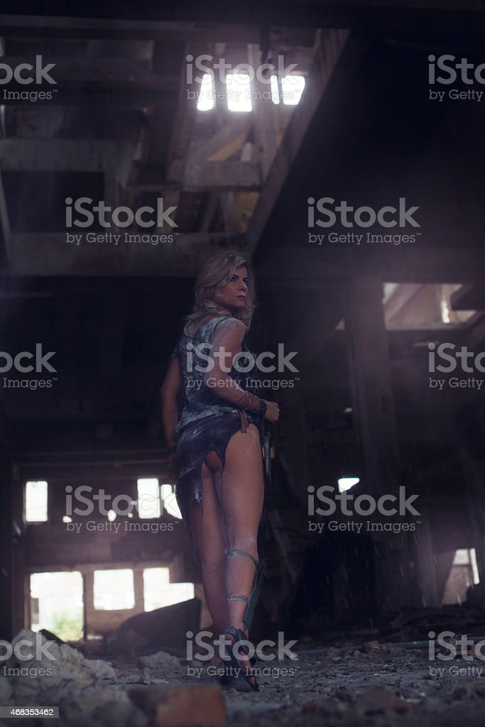 Low angle view of warrior woman walking through ruins. royalty-free stock photo