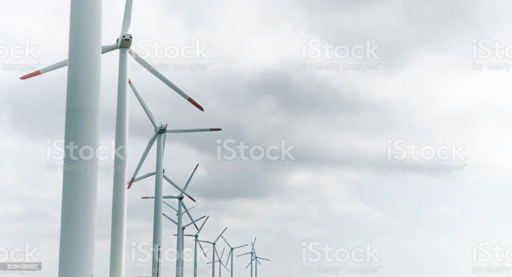 Low angle view of wind turbines in a row stock photo