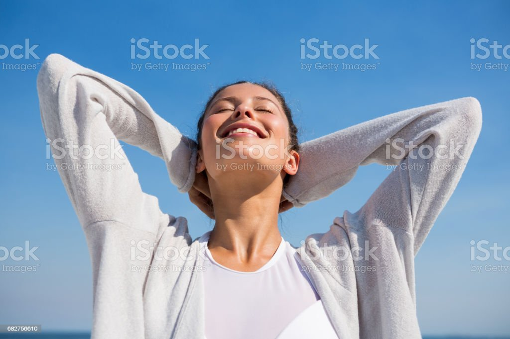 Low angle view of woman with hands behind head stock photo