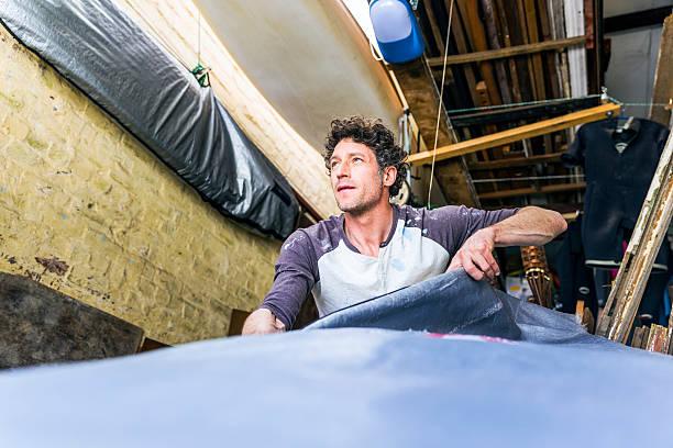 low angle view of worker removing surfboard from cover - surf garage bildbanksfoton och bilder