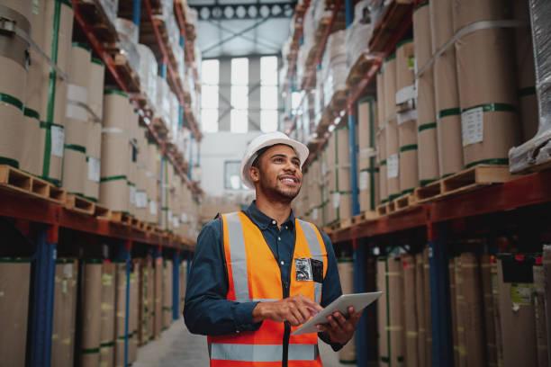 low-winkel-ansicht von jungen afrikanischen mann trägt reflektierende jacke hält digitale tablet stehen im fabriklager lächelnd - fracht stock-fotos und bilder